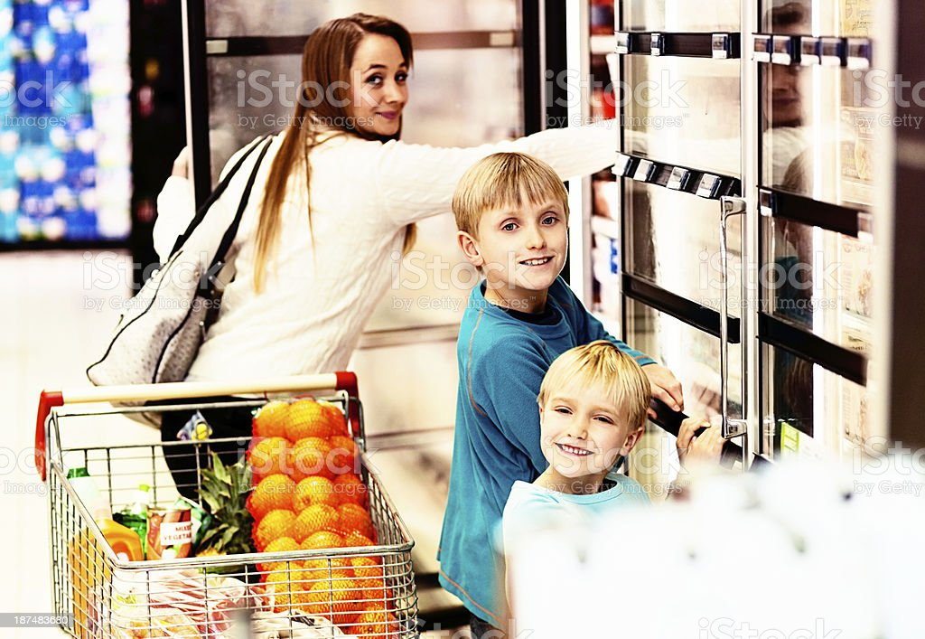Mother, son, and daughter happily shopping together in supermarket royalty-free stock photo