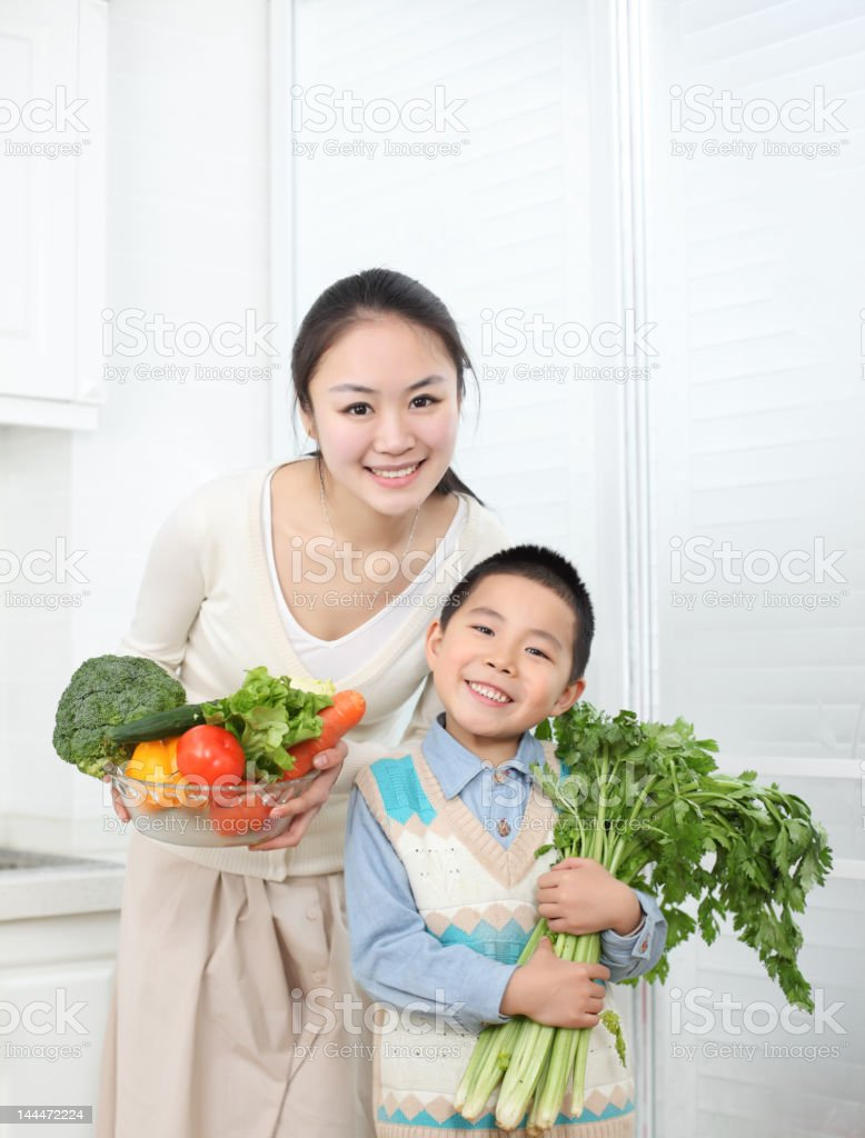 mother , son hold vegetables and fruits in the kitchen royalty-free stock photo