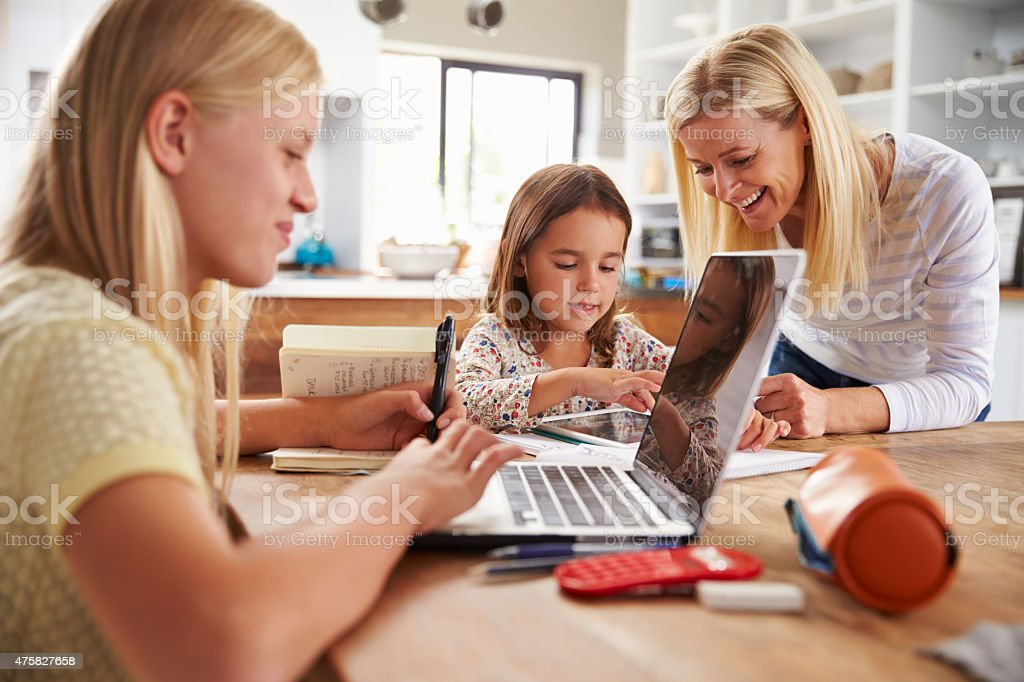 Mother spending time with daughters at home stock photo