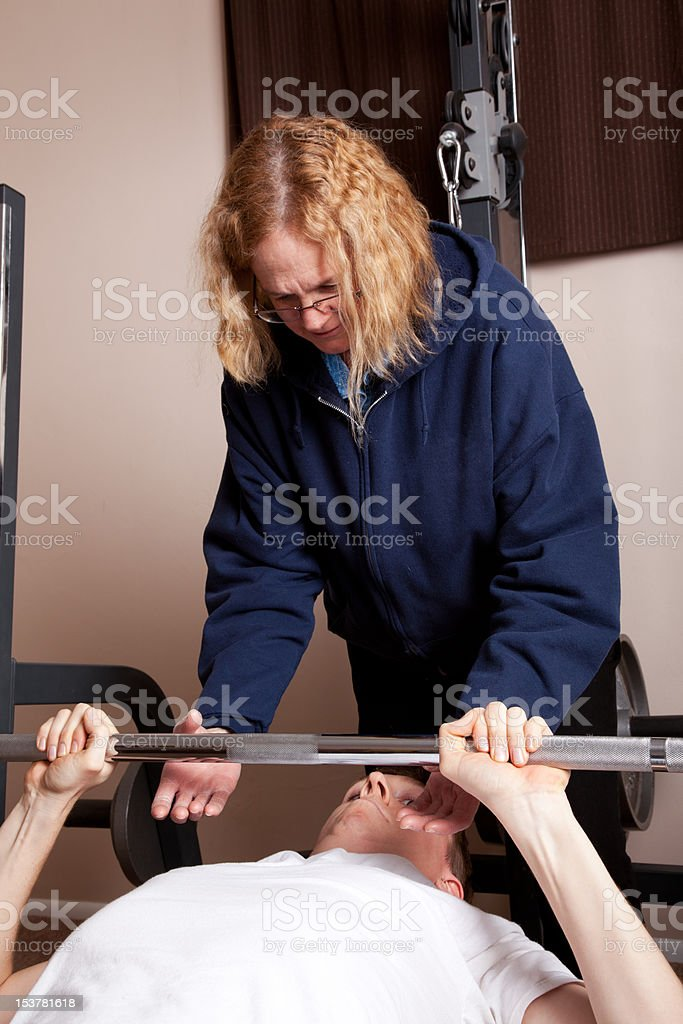 Mother spots son on bench press royalty-free stock photo