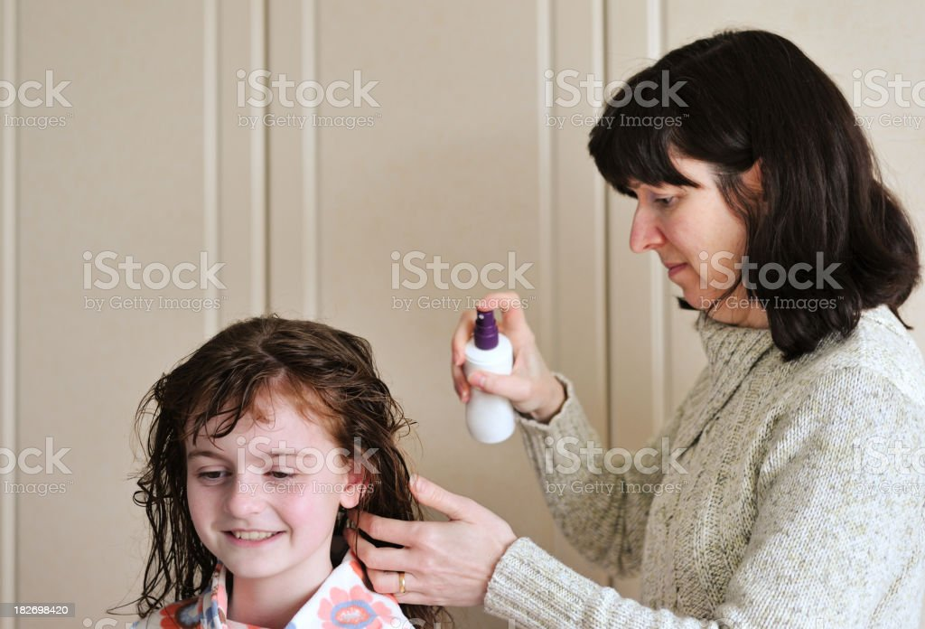 mother spraying child's wet hair with product stock photo