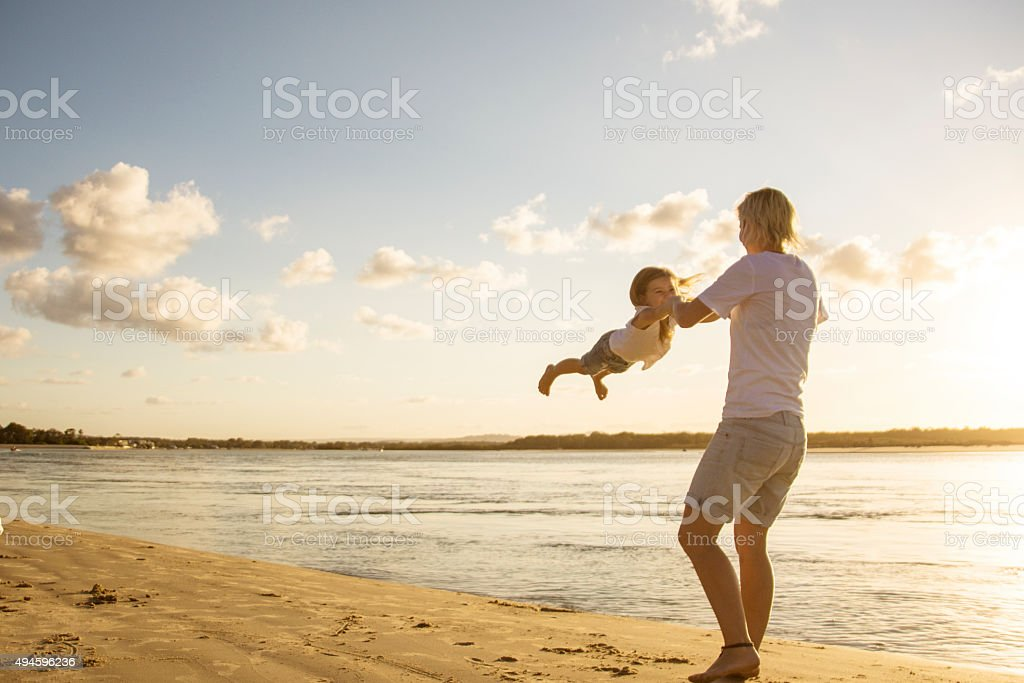 Mother swinging her child in the air stock photo