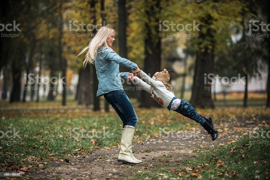 Mother swinging her daughter around in an autumn Park stock photo