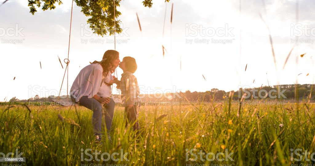 Mother swinging while kissing son on field stock photo