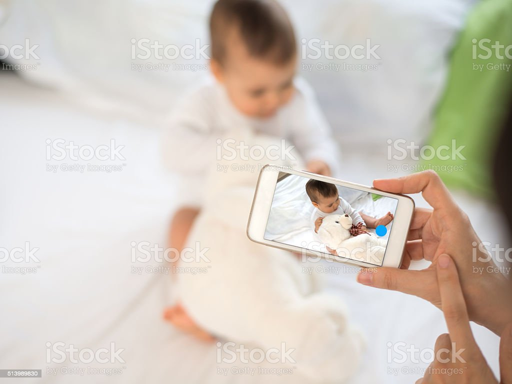 Mother take a photo of her baby with smartphone stock photo