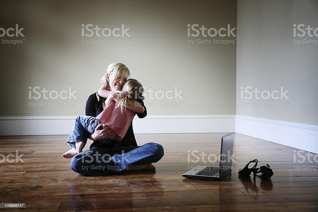 Mother taking a break to hug little girl stock photo