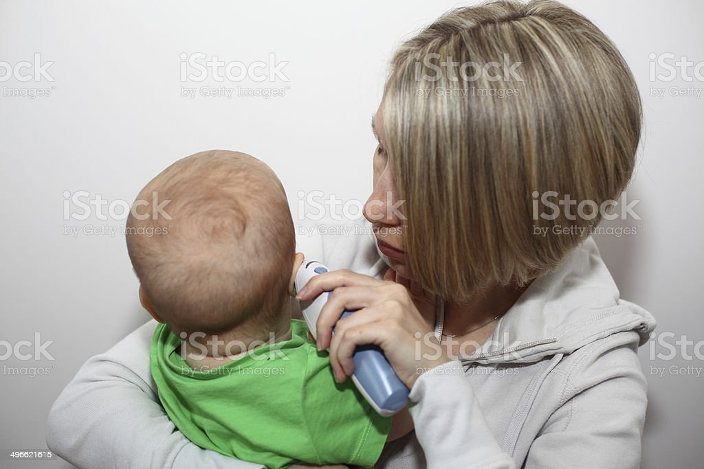 Mother taking baby's temperature stock photo