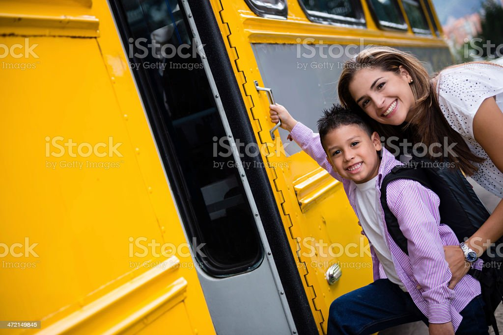 Mother taking boy to the school bus stock photo