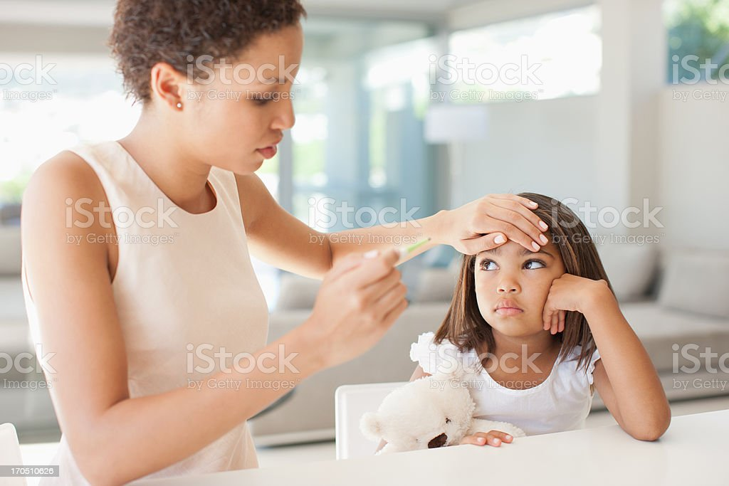 Mother taking daughter's temperature stock photo