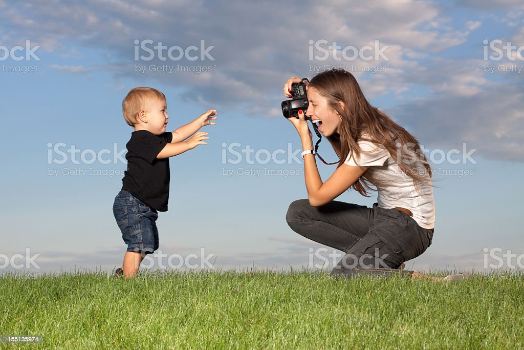 Mother taking pictures of walking child outdoors royalty-free stock photo