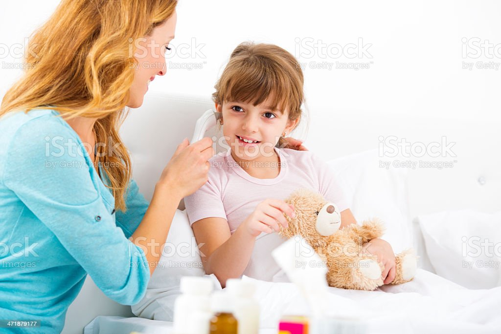Mother Taking Temperature To Her Sick Child. stock photo