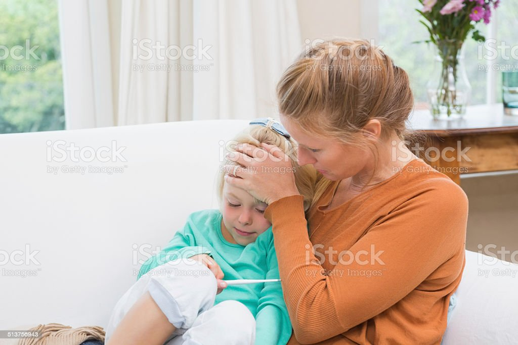 Mother taking the temperature of sick daughter stock photo