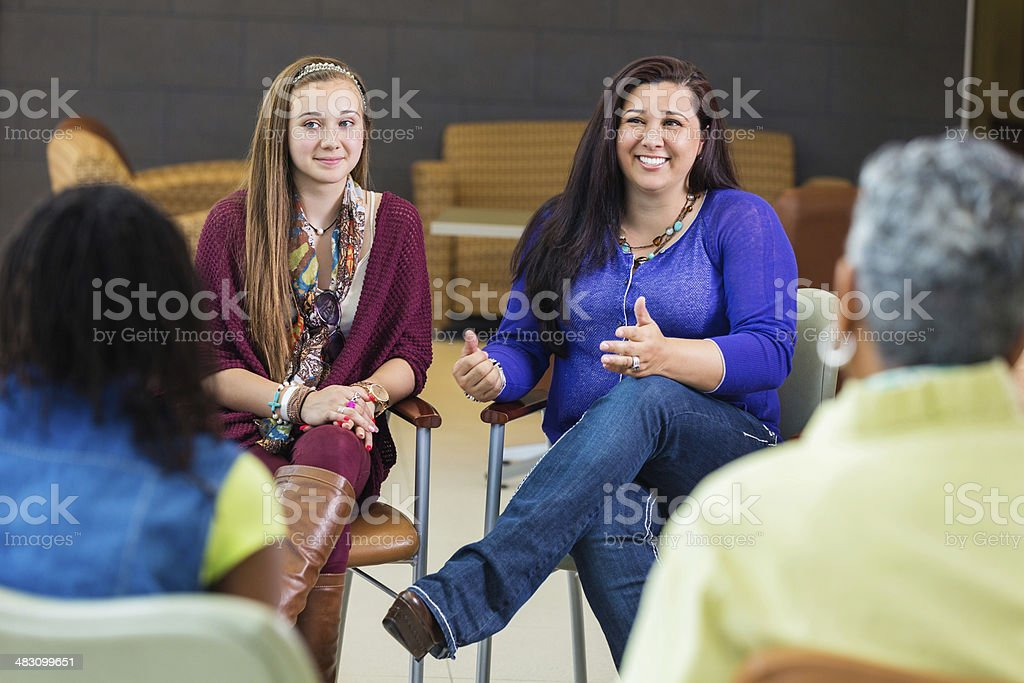 Mother talking about her daughter in parent meeting stock photo