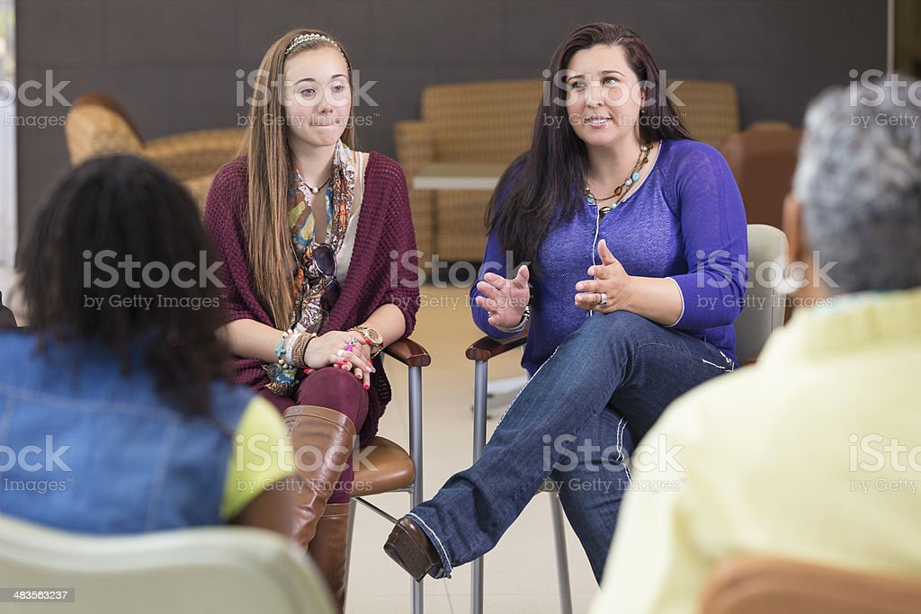 Mother talking about parenting relationship in support group meeting stock photo