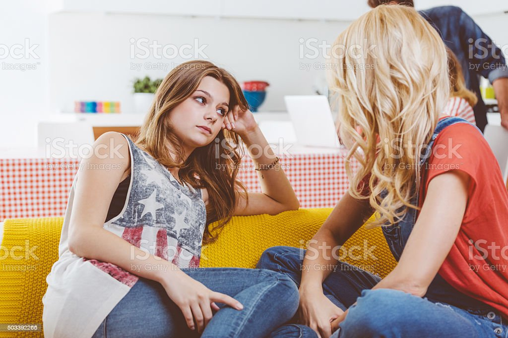 Mother talking with her sad teenage daughter at home stock photo