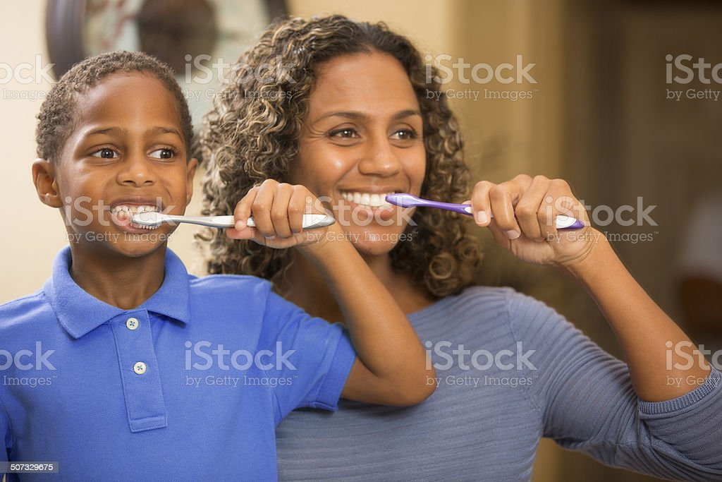 Mother teaches son how to properly brush his teeth. Bathroom. stock photo