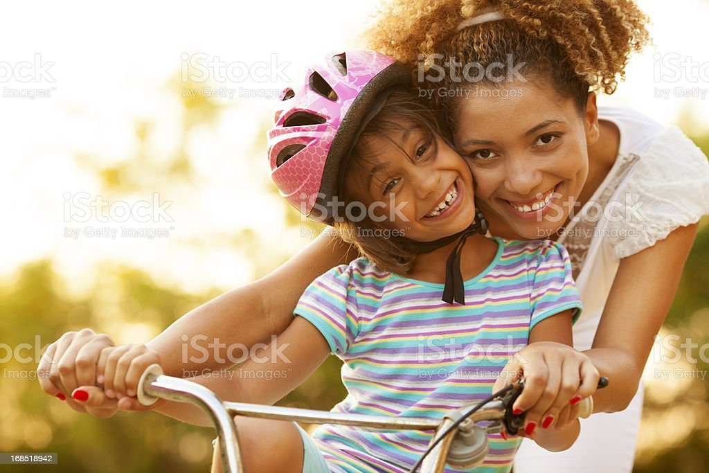 Mother Teaching Child to ride a bicycle royalty-free stock photo