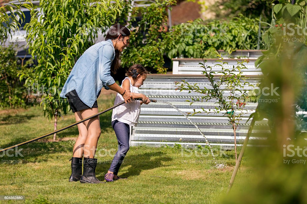 Mother teaching daughter how to water plants outdoors stock photo