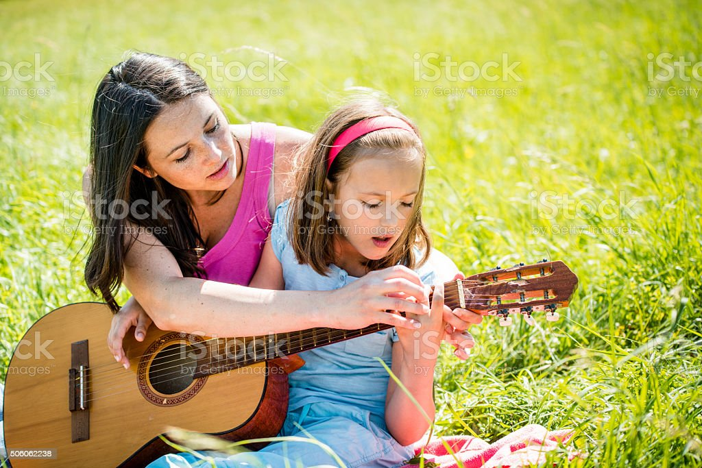 Mother teaching daughter playing guitar stock photo