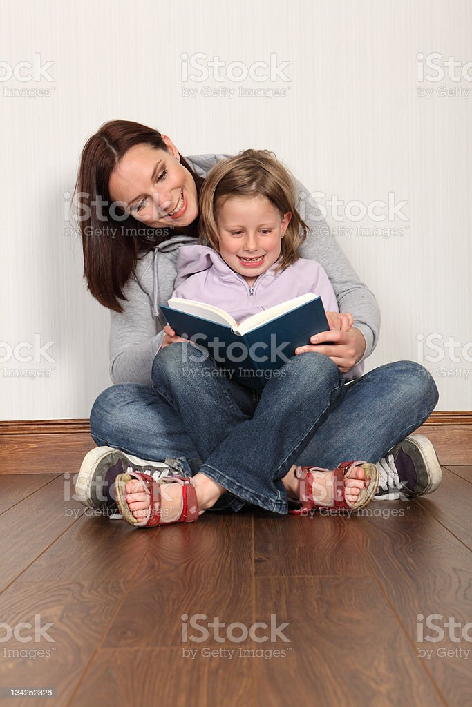 Mother teaching daughter to read home education royalty-free stock photo