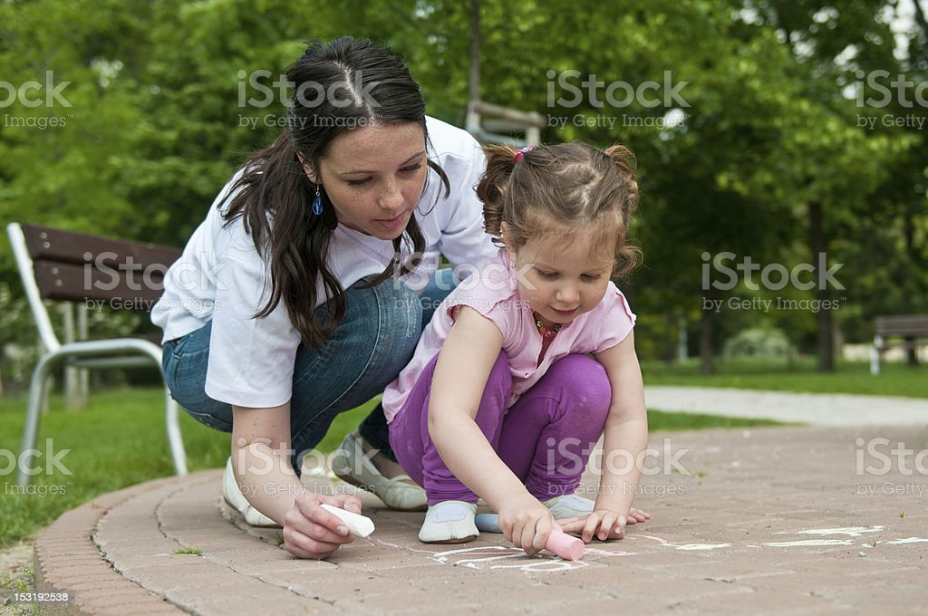 Mother teaching her daughter to draw on the sidewalk royalty-free stock photo
