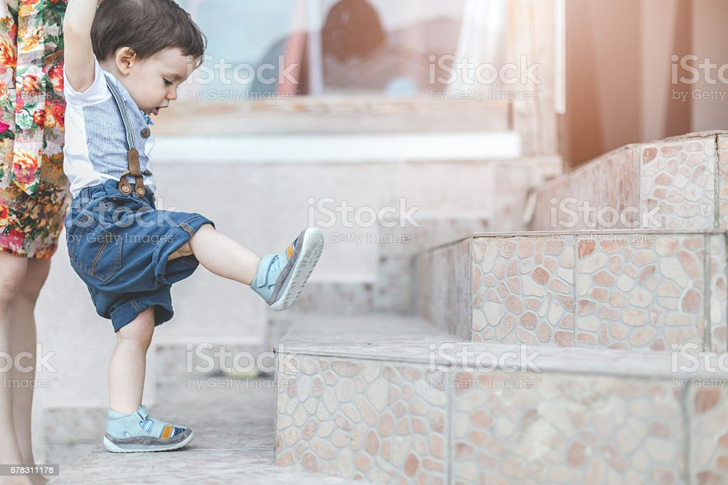 mother teaching her one year old boy to climb stairs stock photo