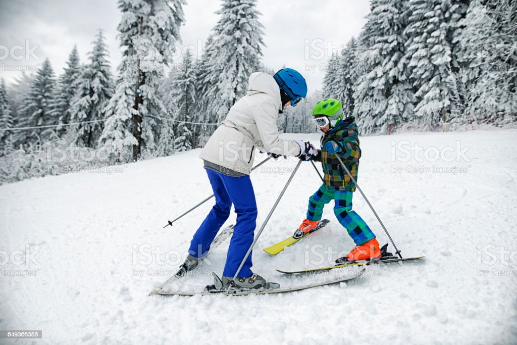 Mother teaching her son skiing stock photo