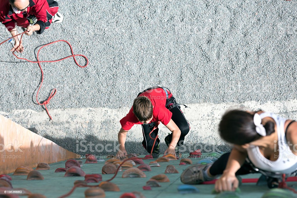 Mother teaching her Son to climbing wall stock photo