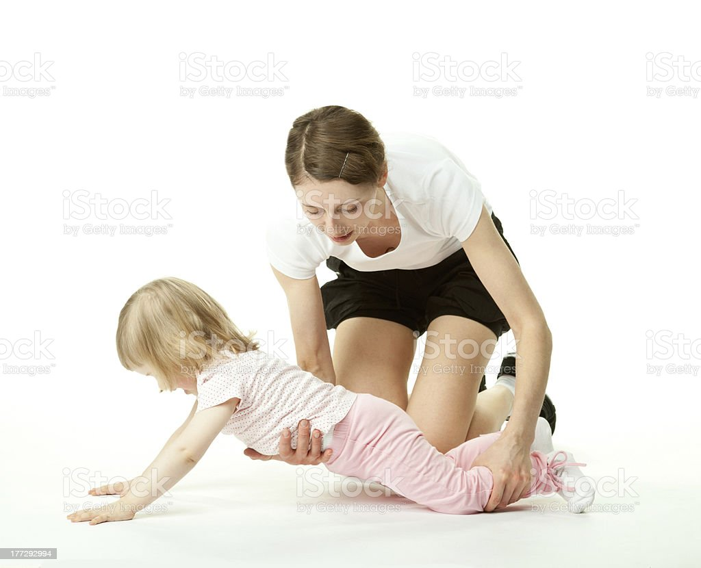 Mother teaching little daughter to do sport royalty-free stock photo