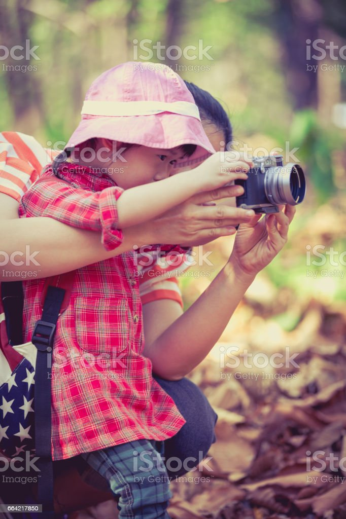 Mother teaching lovely asian daughter taking photos. Outdoors. stock photo