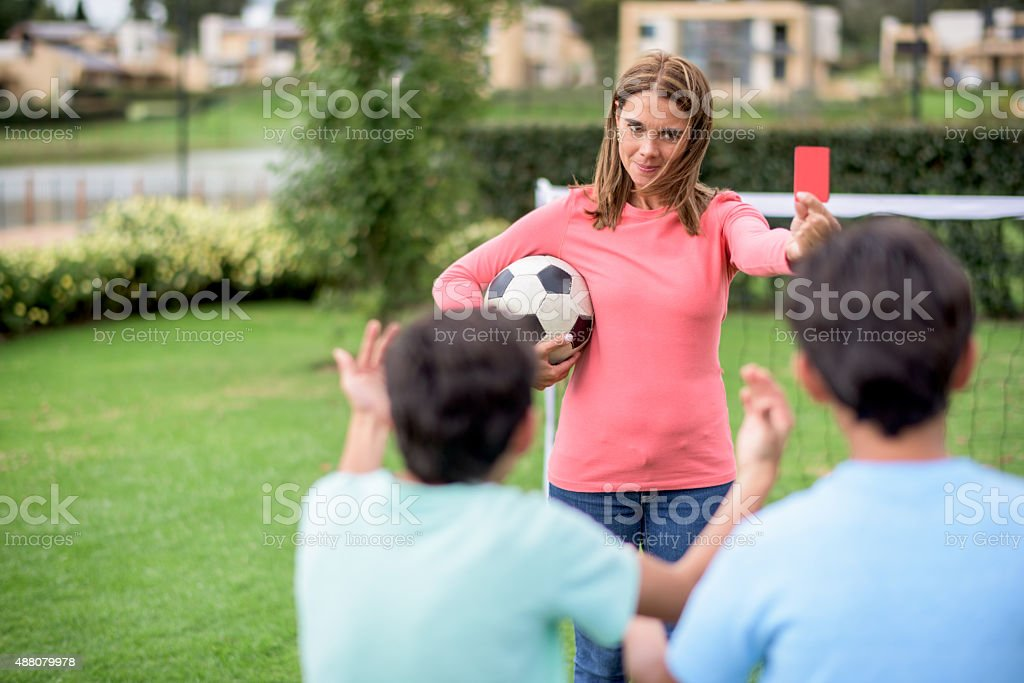 Mother telling off her sons while playing football stock photo