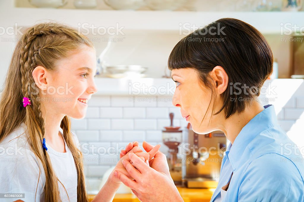 Mother tells fun educating story to daughter in kitchen stock photo