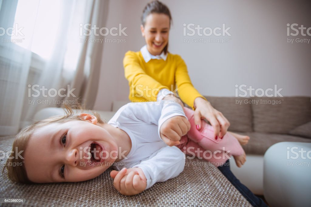 Mother tickling her daughter stock photo