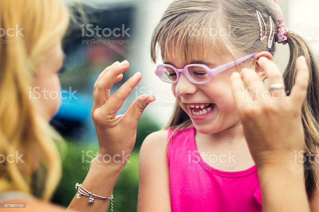 Mother tickling her little daughter outdoors stock photo
