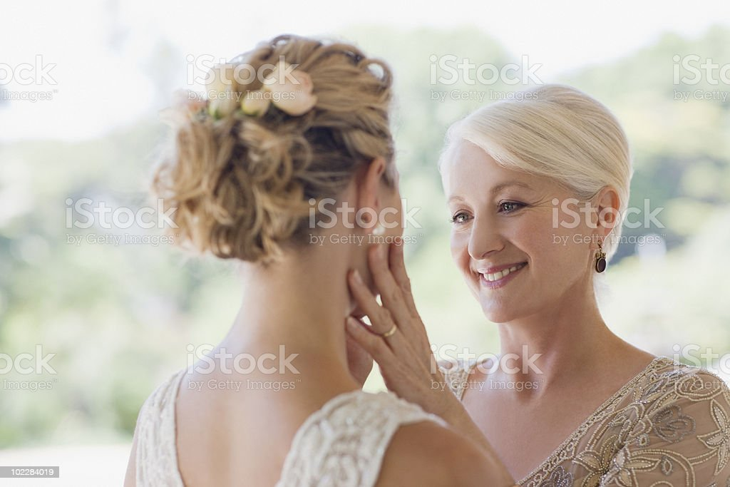 Mother touching brides face stock photo