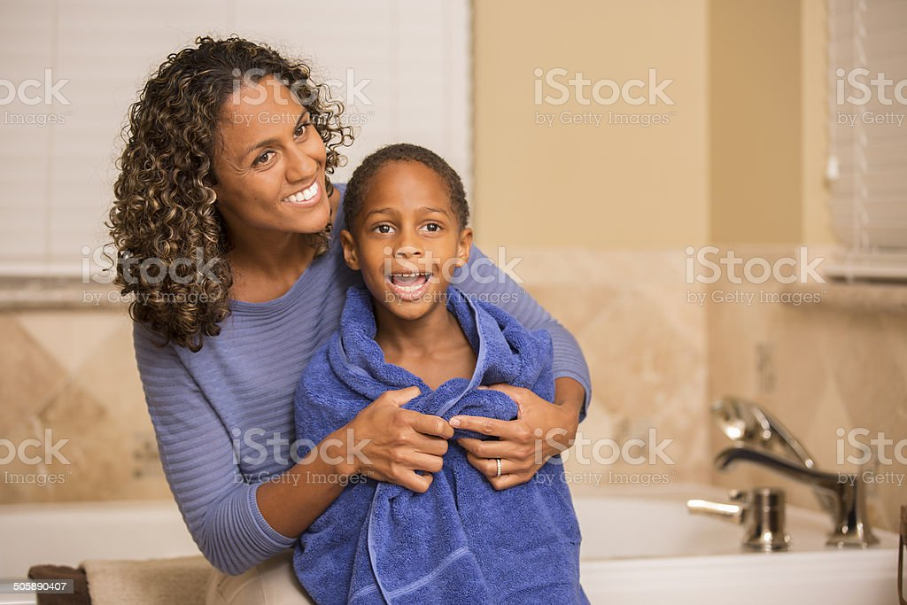 Mother towel dries son after his bath. Home bathroom. stock photo