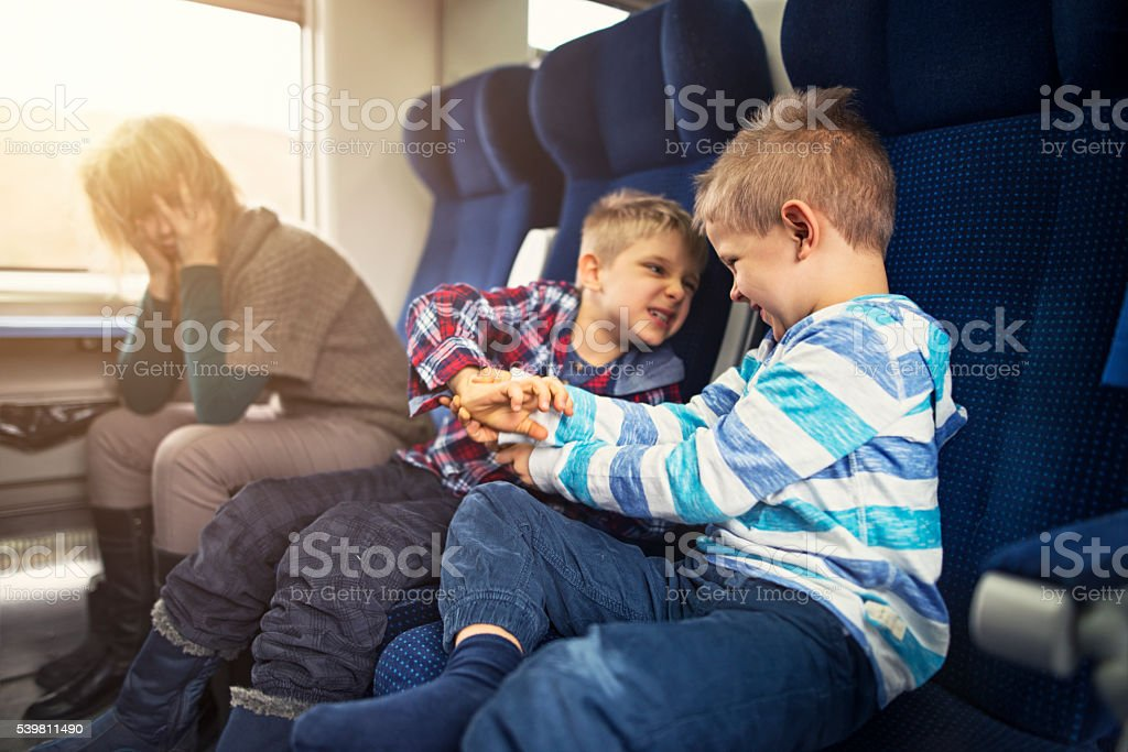 Mother travelling on train with naughty kids stock photo