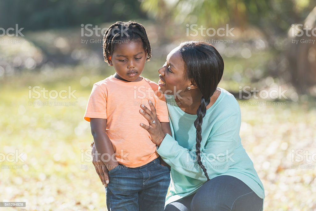 Mother trying to cheer up sad her little boy stock photo