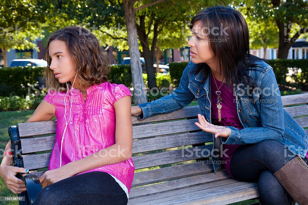 Mother trying to talk with teenager, who is ignoring her royalty-free stock photo