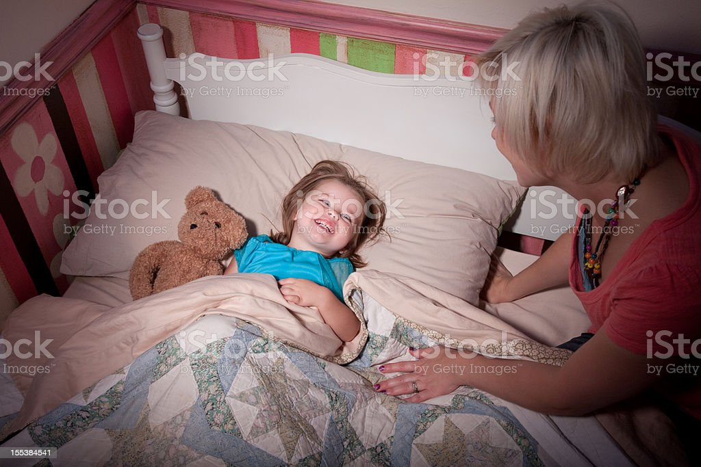Mother Tucking Child in Bed royalty-free stock photo