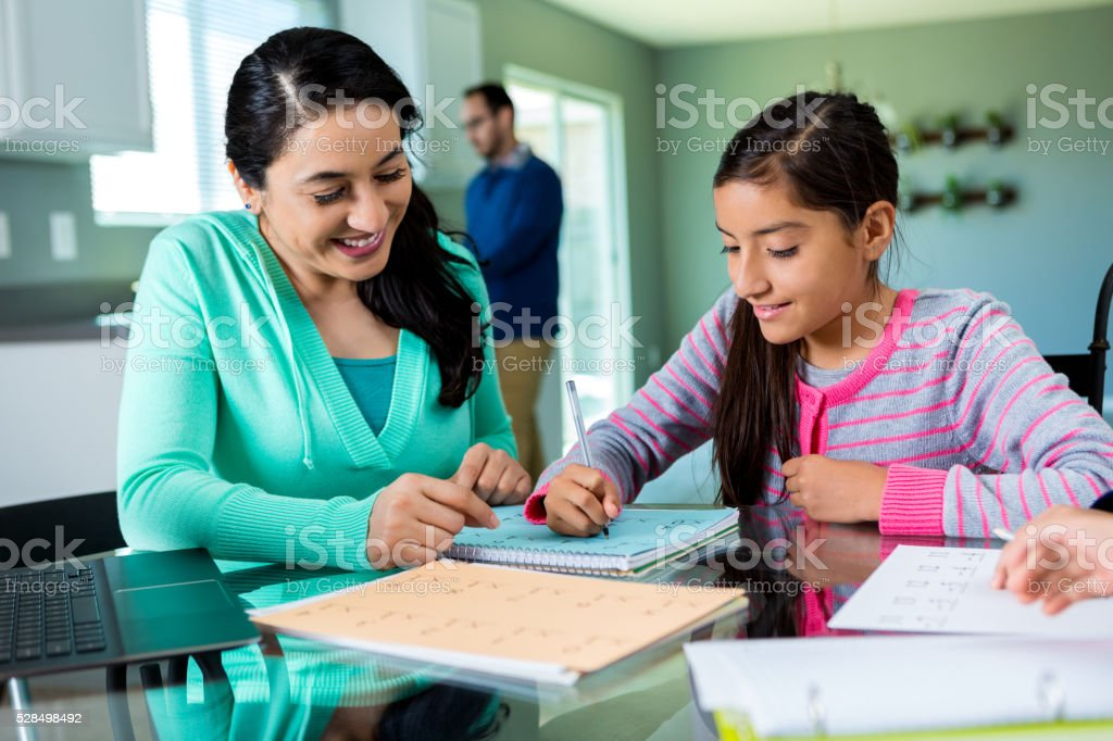 Mother tutoring daughter in kitchen stock photo
