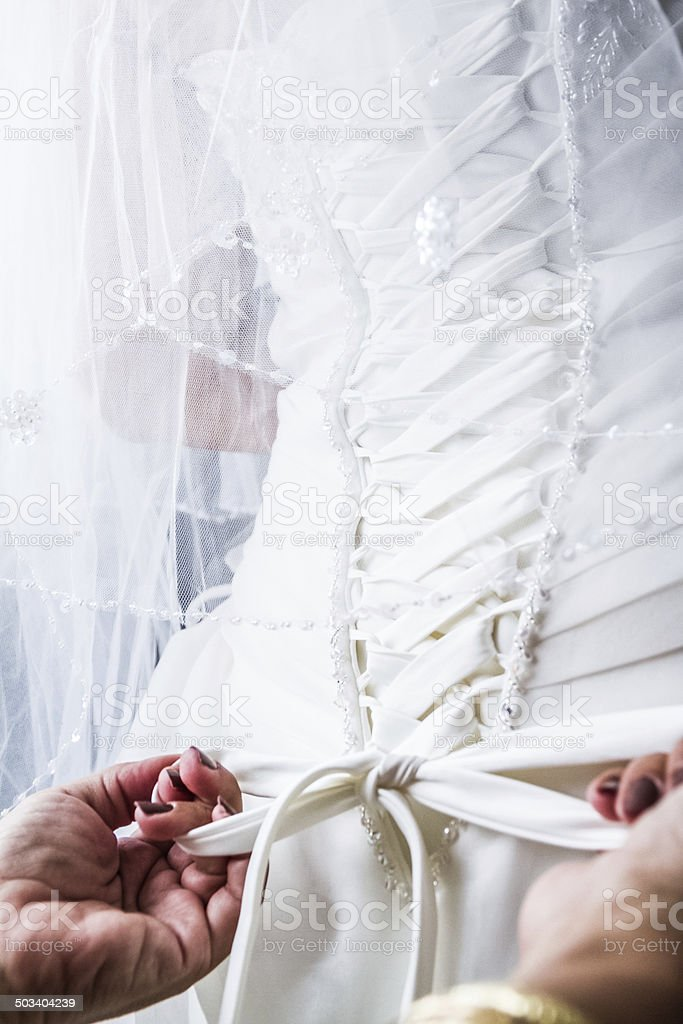 Mother Tying the Bride's Wedding dress stock photo