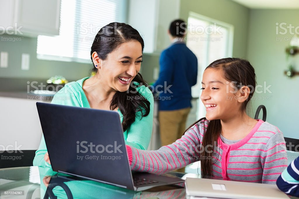 Mother uses laptop as she homeschools daughter stock photo