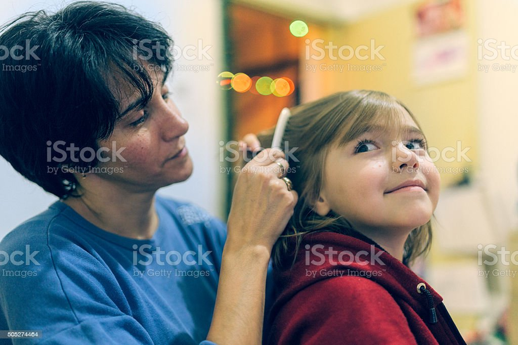 Mother using a comb to look for head lice stock photo