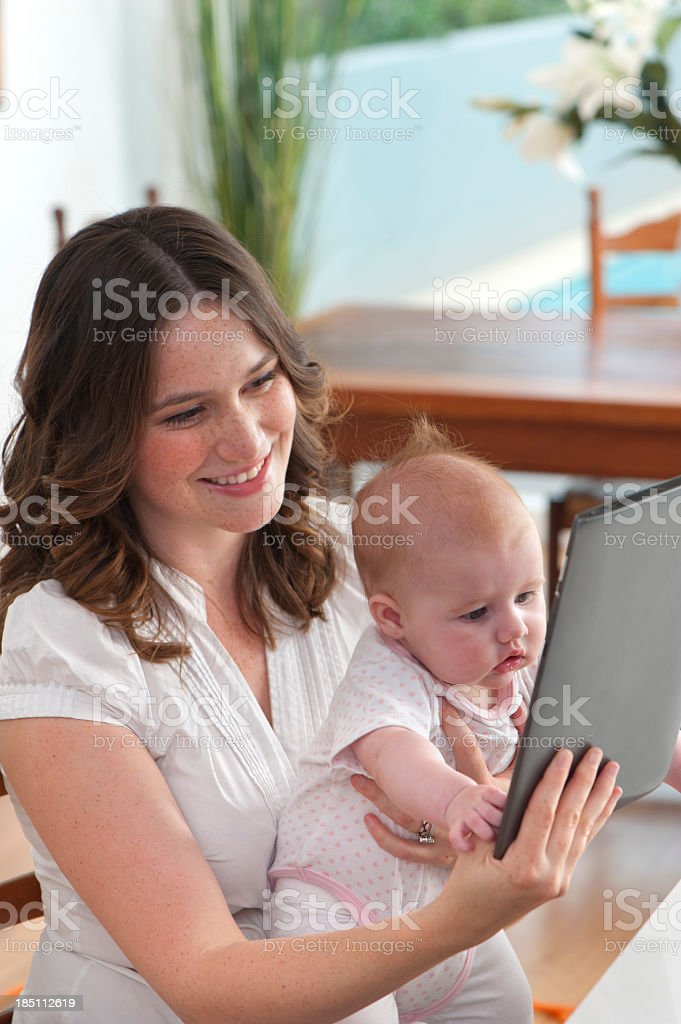 Mother using digital tablet with baby royalty-free stock photo