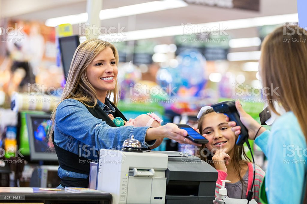 Mother using smart phone to pay for purchases in store stock photo