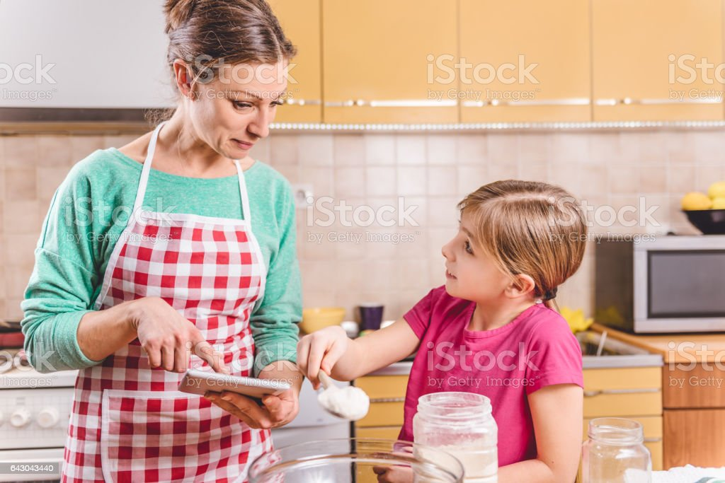 Mother using tablet in the kitchen with daughter stock photo