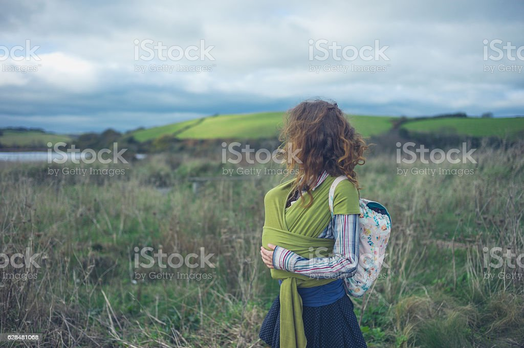 Mother walking in countryside with baby in sling stock photo