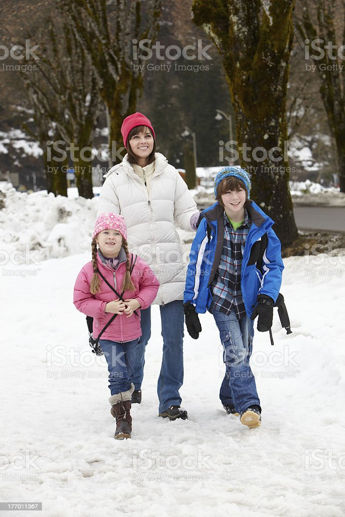 Mother Walking Two Children To School Along Snowy Street royalty-free stock photo