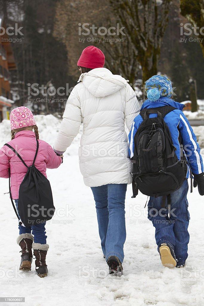 Mother Walking Two Children To School Along Snowy Street stock photo
